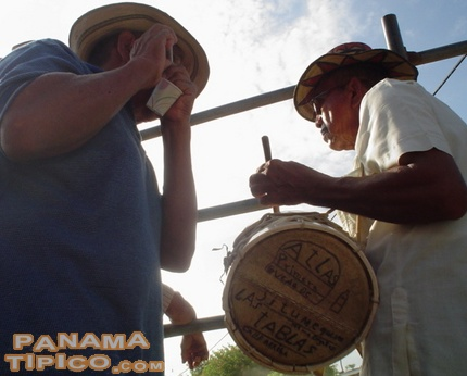 [Drum and flute are played around the fenced area of the bullfight.]