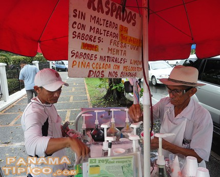 [The raspao is commonly sold from small carts which hold all necessary ingredients and tools.]