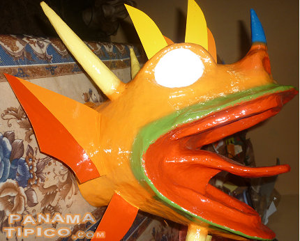 [Now, our mask is halfway painted. Some wood details such as horns and antennae have been added, but the teeth haven't, yet.]