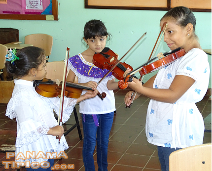 [Kids were divided up according to their main folk interest. Here we see some of them practicing on the violin.]