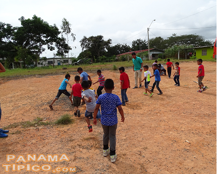 [In front ot the school and church there is a dirt square that kids use for playing sports and other games.]