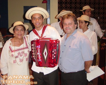 [One of the recent winners with his prize, a brand-new luxury accordion.]