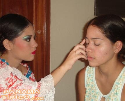 [One of the empolleradas, helping to put some makeup to another one]