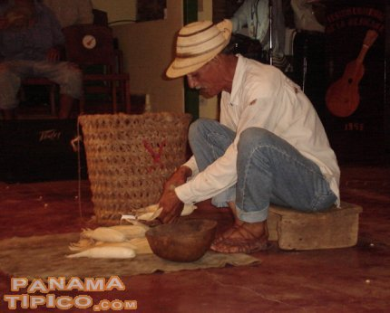[One of the male contestants separates the corn grains as part of his performance during the event.]